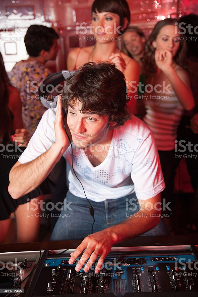 Disc jockey in nightclub with people dancing around him smiling stock photo