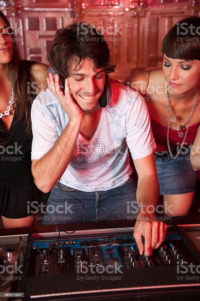 Disc jockey in nightclub with two women  behind him smiling stock photo