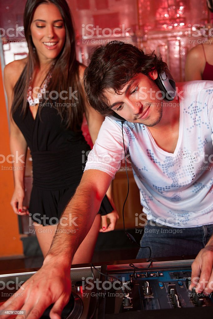 Disc jockey in nightclub with woman dancing behind him smiling stock photo