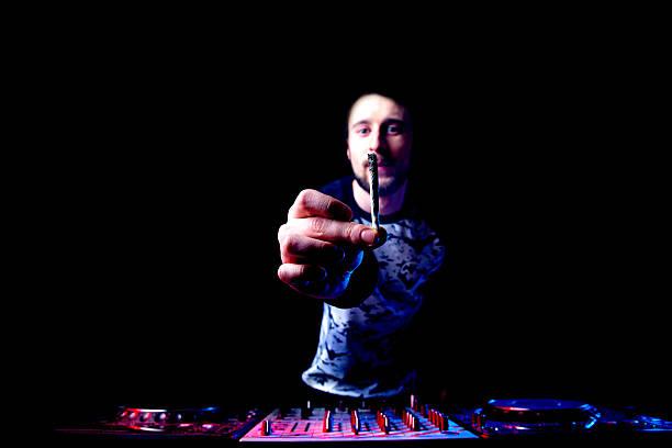 Disc jockey mixing music and smokes joint stock photo