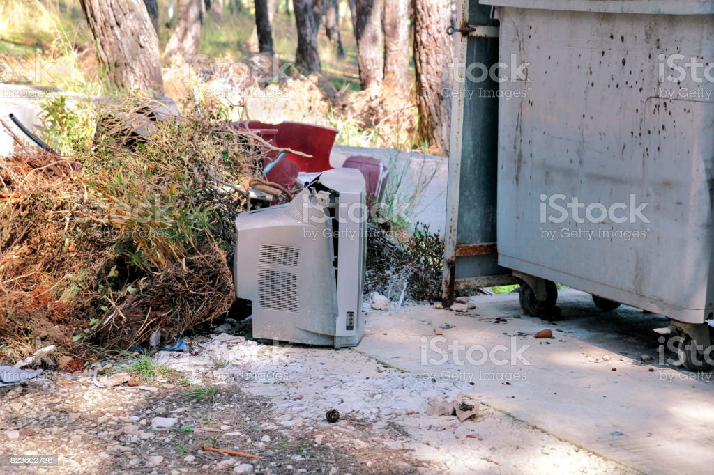 Descarte velhos televisores em uma rua, televisão perto do recipiente de lixo descartado, ambiente natural. Uma TV jogada fora com o lixo. Jogando fora o lixo. Indústria de reciclagem. Ecologia. Não de ecologia. foto royalty-free