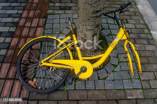 Shanghai, China - Mar 22, 2020: Discarded and abandoned bicycle of popular bike-sharing company ofo beside the road in Shanghai China. Founded in China, Ofo is the world's first and once the largest station-free bike sharing platform