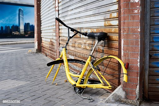 Shanghai, China - April 08, 2017: Discarded and vandalized bicycle of popular bikesharing company ofo laying in the street