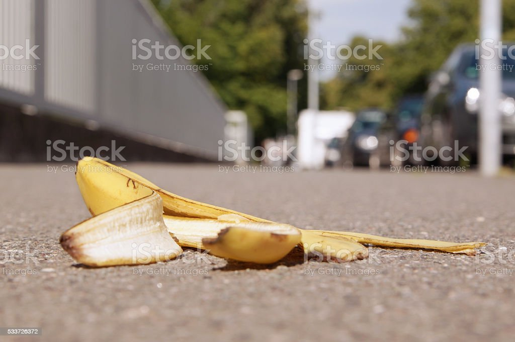 discarded banana skin on pavement stock photo
