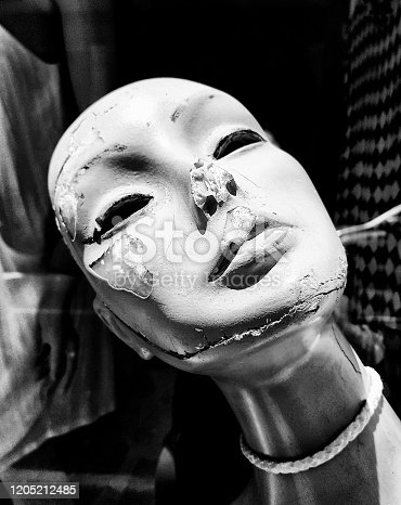 The tragedy of age: a once-beautiful female window mannequin, now discarded, cracked and useless.