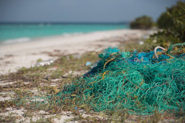 Discarded fishing 'Ghost Net' on beach Net found on Maldives island  Beach; which is harmful to marine and coastal life fishing line stock pictures, royalty-free photos & images
