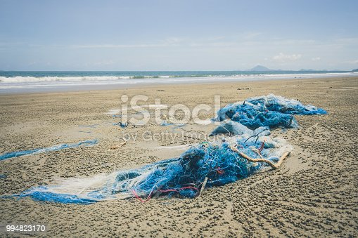 Discarded fishing net and rope have been washed up on the beach at Ko Lanta, Krabi, Thailand.  These abandoned or obsolete items become dangerous garbage, polluting the Ocean, referred to as 'Ghost Nets.'  Ghost Nets are responsible for the deaths of huge amounts of Marine Life every year, through entanglement and consumption.