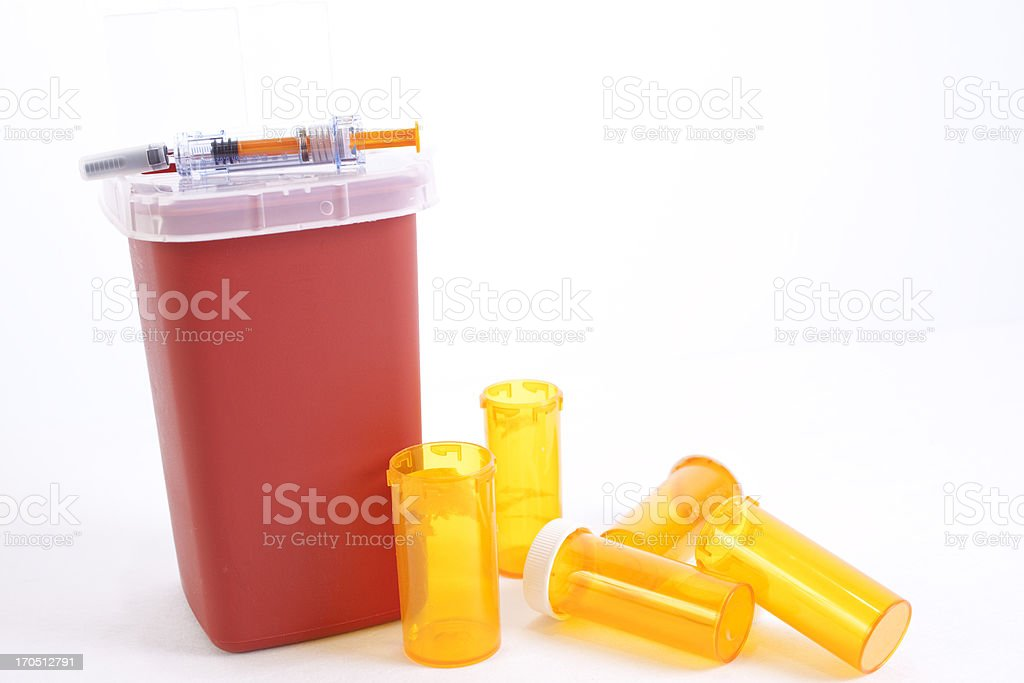 Discarded meds.  Empty medicine bottles and syringe. Sharps container. stock photo
