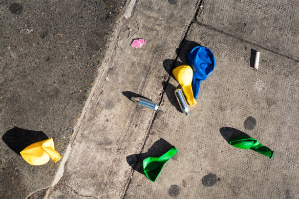 Discarded nitrous oxide canisters and balloons on a London street Metal nitrous oxide canisters and balloons discarded on a street in Shoreditch, East London, following use of the so called 'Legal High'. nitrous oxide stock pictures, royalty-free photos & images