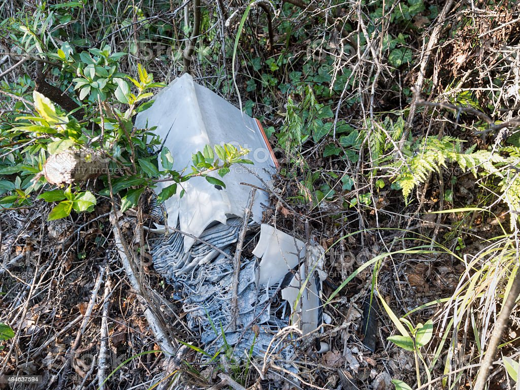 Discarded old car battery falling apart in hedge. stock photo