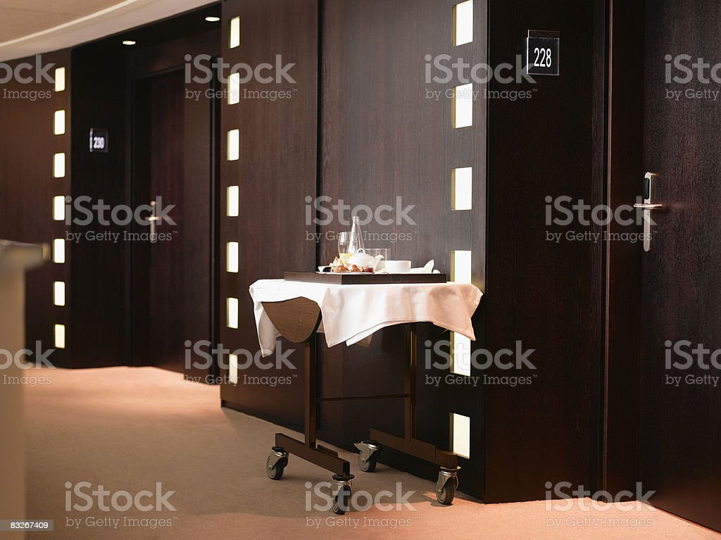 Discarded room service dishes in hotel corridor stock photo