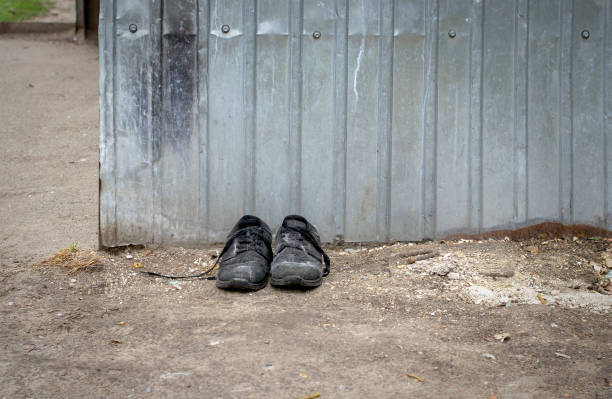 Discarded shoes. Old shoes by the dumpster. stock photo