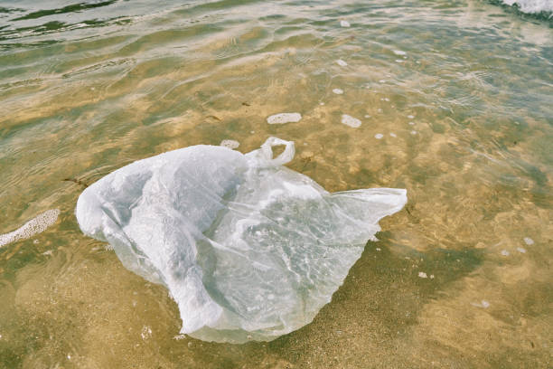 discarded white plastic shopping bag floating in the sea. - trash stock pictures, royalty-free photos & images