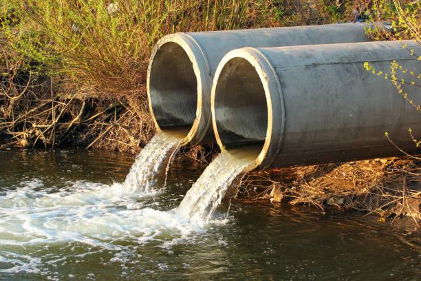 einleitung von abwasser in einen fluss - kanalisationsabflüsse stock-fotos und bilder