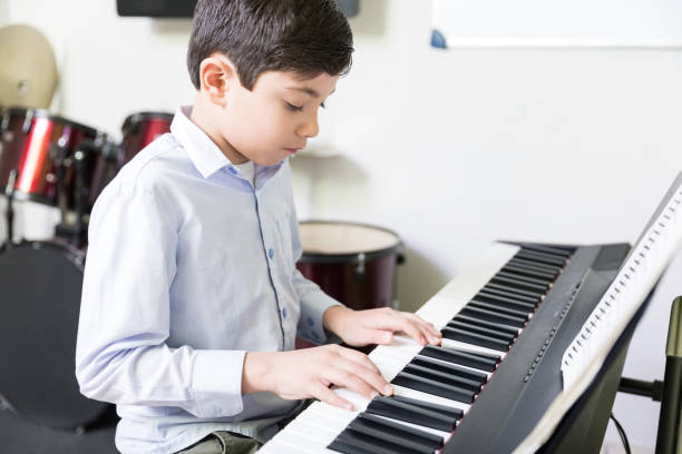 Disciplined Boy Practicing In Piano Class Confident male student learning to play electric piano in music school keyboard player stock pictures, royalty-free photos & images