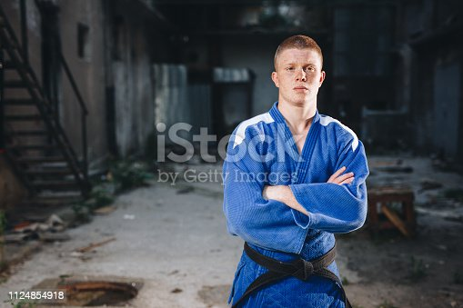 Strong and confident judo athlete exercising outdoors.