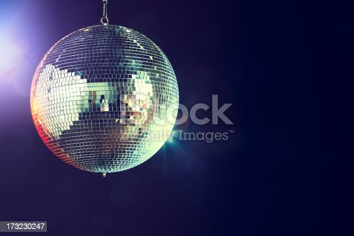 A shining disco ball glitters and spins in a dance club at night, reflecting the various colored lights.  Horizontal with copy space.