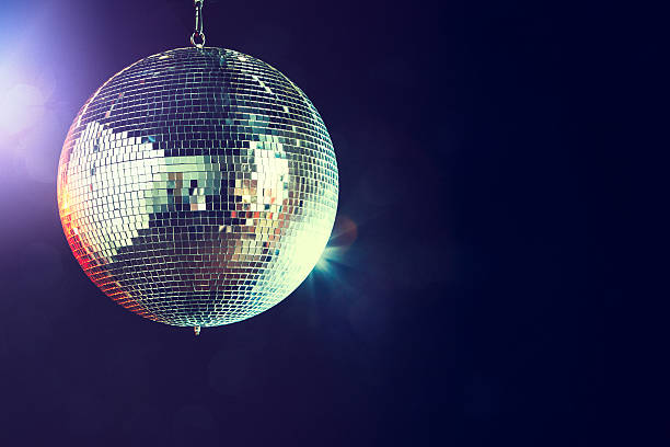Disco Ball A shining disco ball glitters and spins in a dance club at night, reflecting the various colored lights.  Horizontal with copy space. nightclub stock pictures, royalty-free photos & images