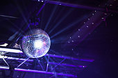 Disco ball with bright purple rays, night party background photo