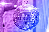 Disco ball with bright rays of lights, party background