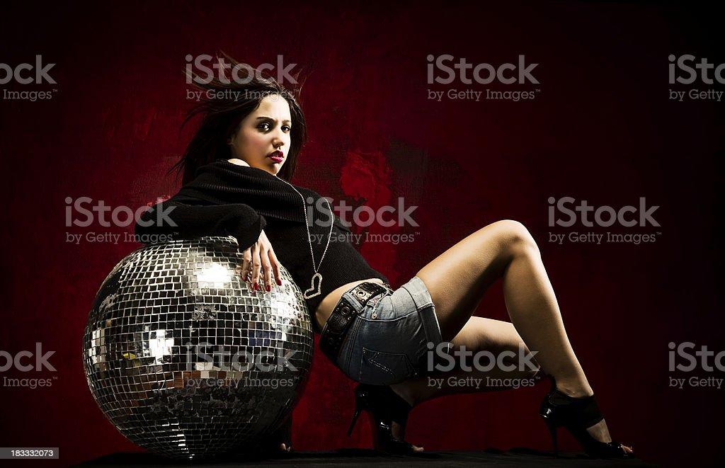 Young woman leaning the disco ball..studio shot.