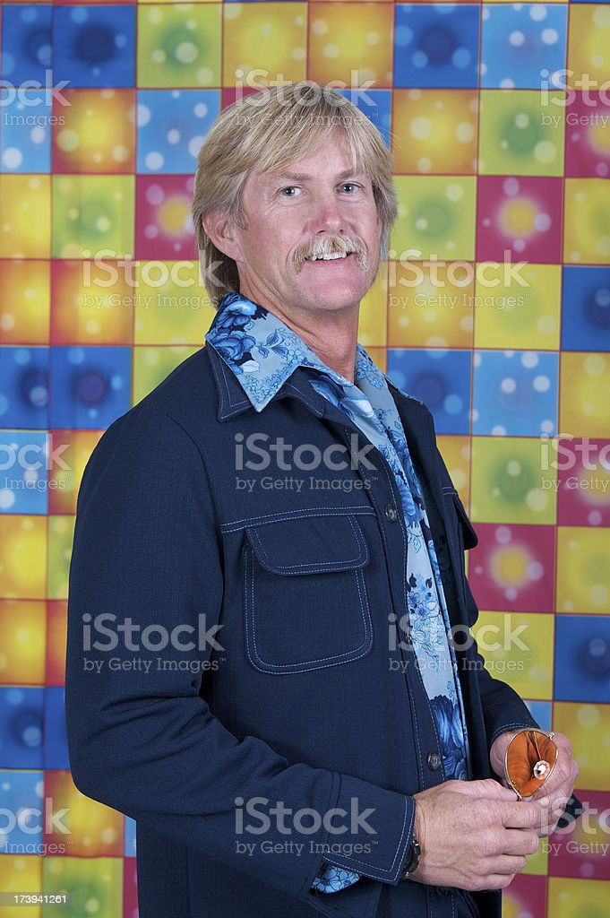 Disco Man in Leisure Suit Holding Sunglasses stock photo