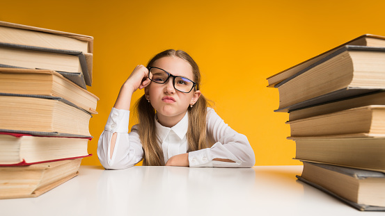 istock Discontented Primary School Girl Sitting Between Book Stacks On Yellow 1169135027