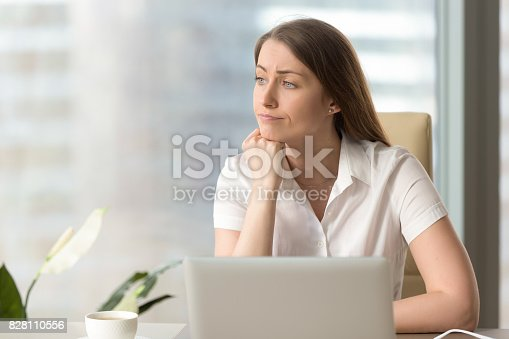 istock Discontented thoughtful woman holding hand under chin bored at workplace 828110556