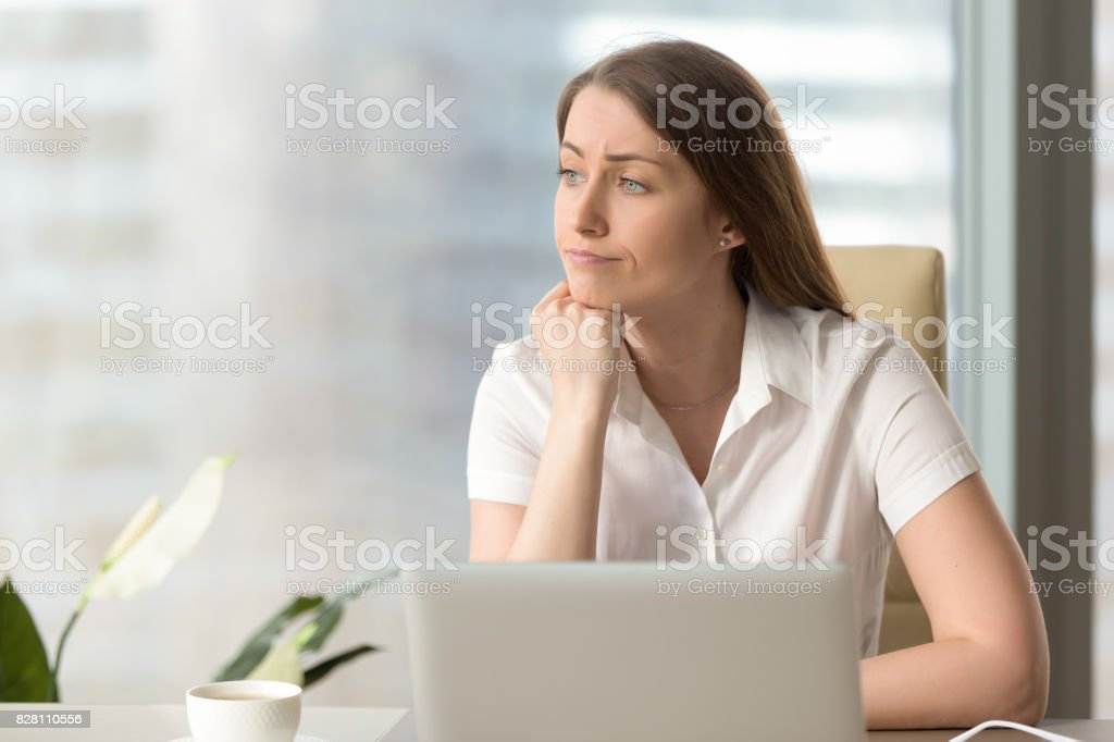 Discontented thoughtful woman holding hand under chin bored at workplace stock photo