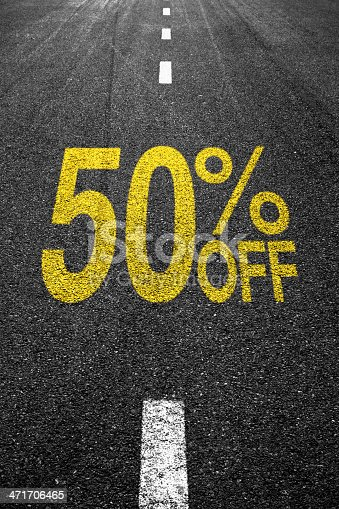 Discount sale sign on the asphalt yellow text: %50 OFF