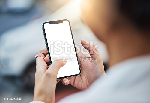 Closeup shot of an unrecognizable businesswoman using a cellphone with a blank screen in the city