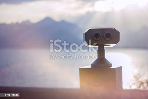 Coin operated binocular in front of cloudy mountain scenery.