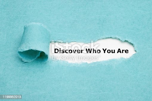 Text Discover Who You Are appearing behind torn blue paper. Finding yourself or personal development concept.