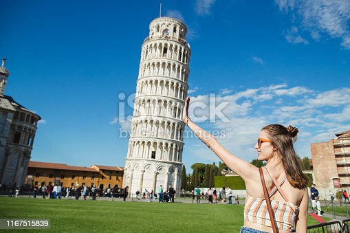 A woman is gesturing with her hands in front of the Leaning Tower of Pisa.