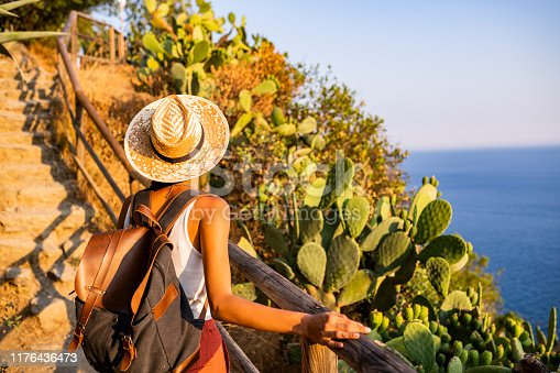 Female tourist walking towards Corniglia village, Beautiful town in Cinque Terre coast. On the way there she enjoys the view on the sea