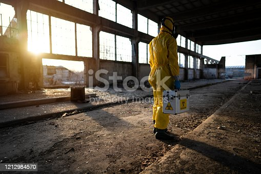 Man in protective workwear examining radioactive ruined building.