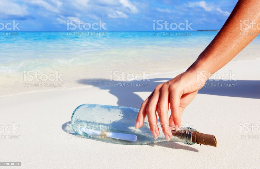 Hand picking up a message in a bottle found on a tropical beach.