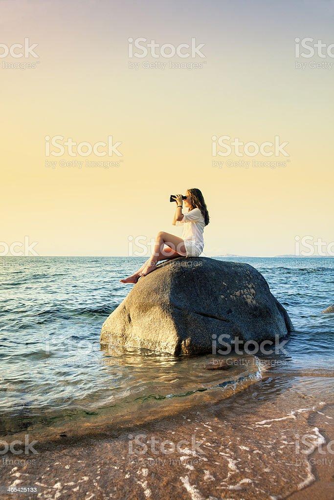 Girl in the beach with binoculars.