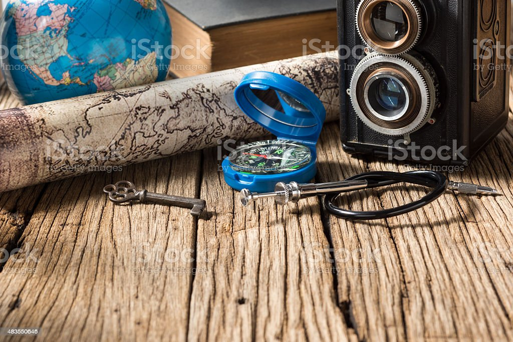 compass map camera globe key and book with space of old wood in...