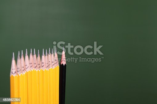 A black pencil with a sad face at the end of a line.  All other pencils are yellow.