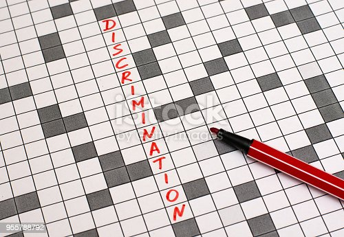Discrimination. Text in crossword. Red letters. Close-up