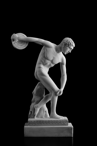 A stone statue of discus thrower on a black background