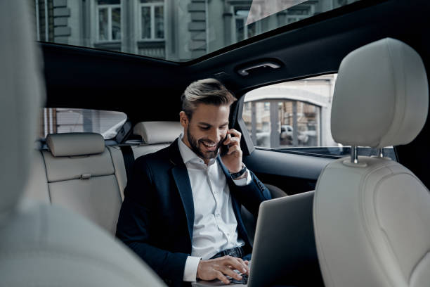 Discussing business details. Handsome young man in full suit talking on smart phone and smiling while sitting in the car on the move stock pictures, royalty-free photos & images