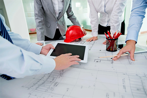 Group of architects and engineers discussing construction plans around a table.