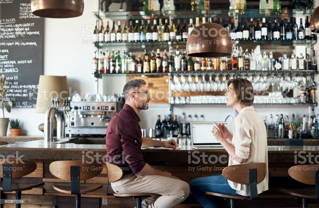 Cropped shot of two businesspeople working together in a local cafe