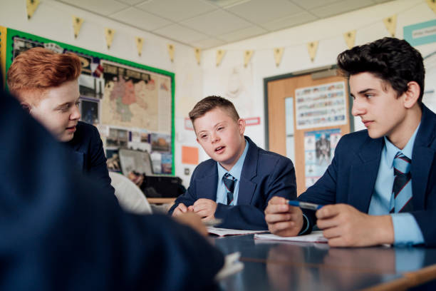 Discussing in Class Group of teenage males discussing during class. learning difficulty stock pictures, royalty-free photos & images