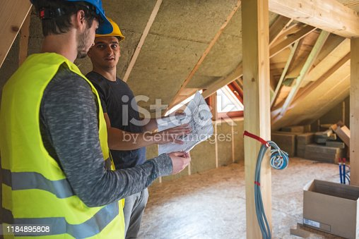 Construction workers reviewing blueprint at construction site.Roof with mineral rockwool in wall section. House under construction with insulation glass wool on an attic floor