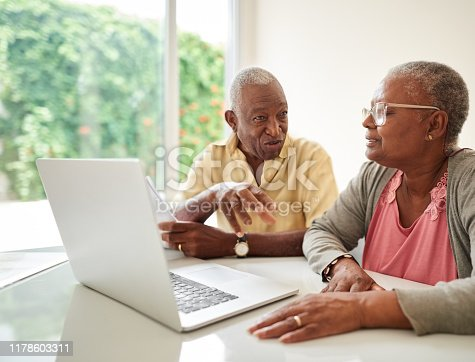 Shot of a senior couple with financial documents and laptop at home