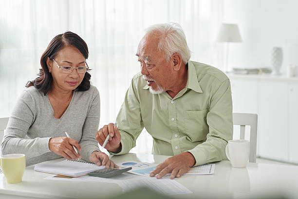 Discussing papers Senior Asian business couple discussing financial documents vietnamese ethnicity stock pictures, royalty-free photos & images