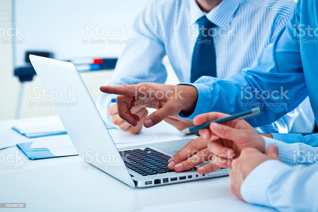 Discussing project Three businessmen discussing project on the laptop. Close-up on hands. Adult Stock Photo